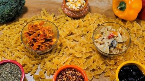 Raw farfalle pasta falling on fusilli pasta kept on a wooden table - Italian food