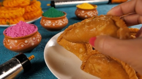 Female hand keeping Gujiya - sweet dumplings made during the festival of Holi