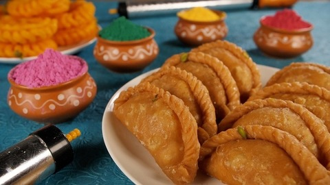 Happy Holi Concept - Tasty Gujiya kept on a white plate with powder Holi colors