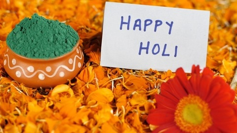 Happy Holi greeting card kept along with Gulal wishing for the popular occasion