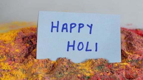 Handmade greeting card to wish Holi dropping on mixed Gulal (Holi colors)