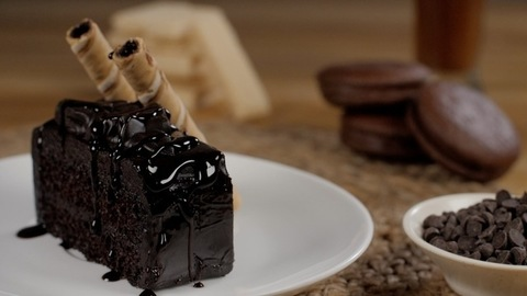 Chocolate syrup falling on a slice of chocolate pastry decorated with sweet wafer tubes