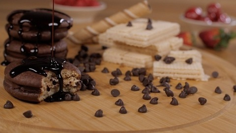 Fresh chocolate syrup falling on soft cream-filled cookies - a delicious dessert