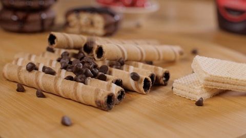 Tasty dark chocolate chips dropping on sweet cocoa cream filled wafer rolls