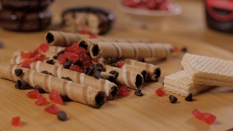 Red-colored sweet fruit candy falling on chocolate cream-filled crispy sticks