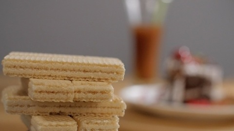 A pile of white cream filled crunchy wafer biscuit snack crackers rotating slowly