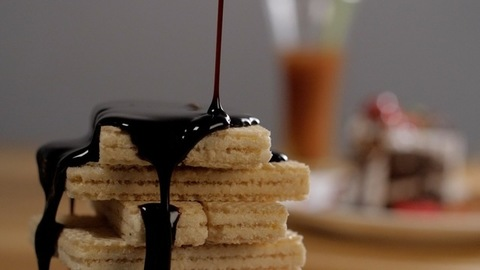 Liquid dark chocolate pouring on white thin biscuit waffles stacked together
