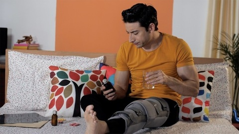 Handsome Indian male having a glass of water while checking his prescribed medicines