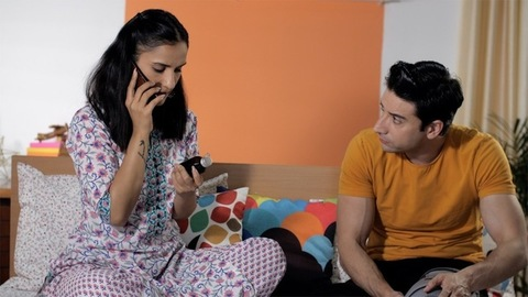 A concerned wife in her nightwear speaking to the doctor using her smartphone