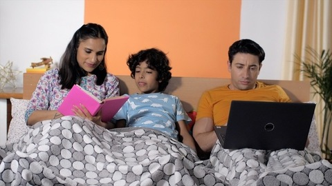 A young father working on laptop in the bedroom at night
