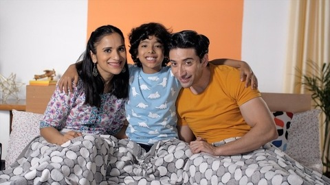 A cheerful-looking Indian father, mother, and son posing in front of the camera