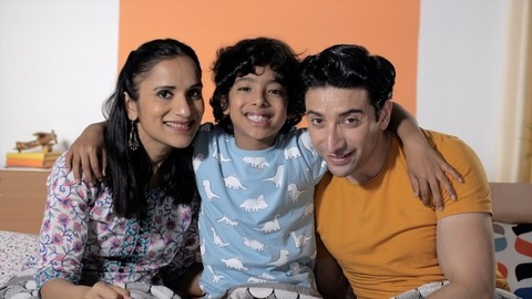 A young couple posing happily for pictures with their sweet and adorable child