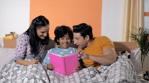 Caring young mom and dad reading a storybook with their adorable child at home