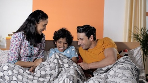 Happy young parents having fun tickling their child sitting together on the bed