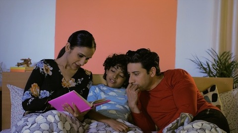 A cheerful Indian mother telling a bedtime story to her adorable child and dad