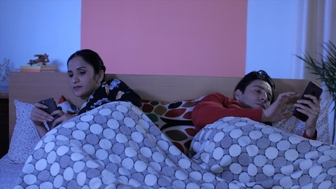 A young couple lying in bed browsing their smartphones before going to bed