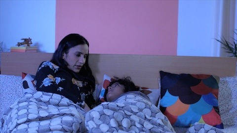 A young mother narrating a bedtime story to her son before sleeping