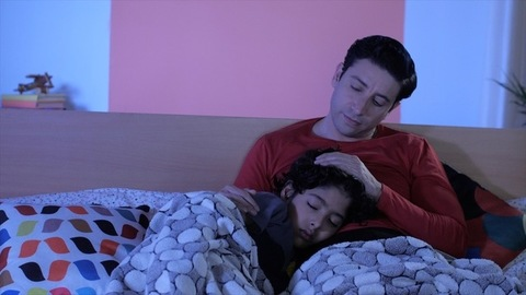 An adorable child sleeping peacefully on his father's lap