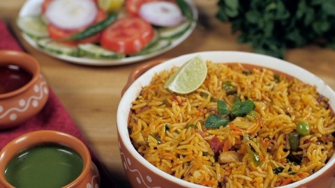 Woman's hand tasting slow-cooked vegetarian Paneer Pulao with a spoon