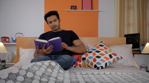 Portrait of a young clean-shaven Indian man reading his favorite storybook at home