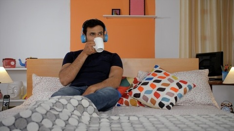 Smart young man having his morning tea / coffee sitting in the bedroom at home