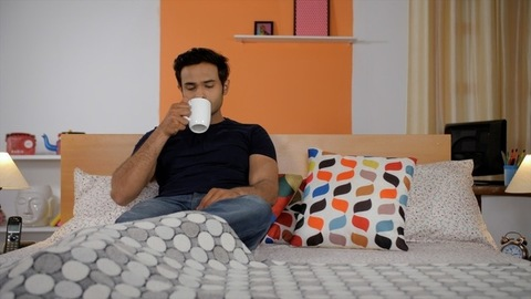 Portrait of a young man with stubble having his morning tea / coffee in the morning