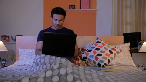 Portrait of a young man in a black T-shirt and blue jeans using his laptop at home