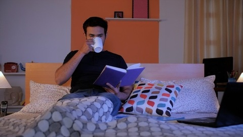 Portrait of a happy young man reading an interesting book sitting on the bed - At night in bedroom