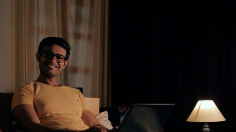 Portrait of a smiling young man in eyeglasses doing a video chat on a laptop
