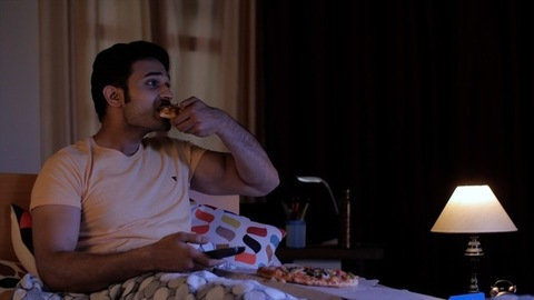Portrait of a young man sitting and relaxing on the bed watching television - Binge eating