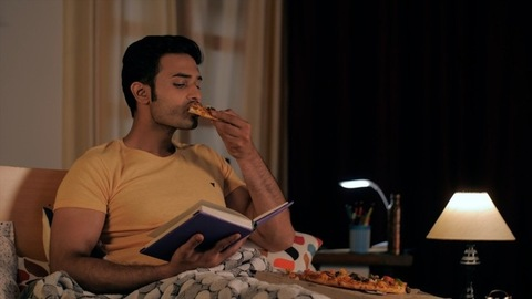 Modern well-groomed boy eating pizza while reading an enjoyable storybook