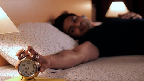 Portrait of an Indian man wearing a black T-shirt looking at the alarm clock