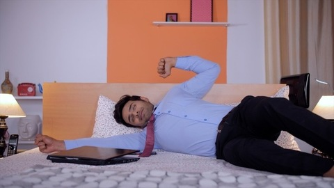 Portrait of a bored businessman resting on his bed after a hard day's work