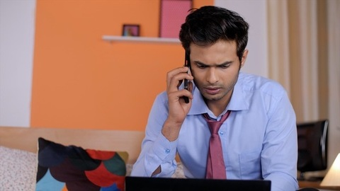 Businessman in formal clothes talking to a colleague on a mobile - work from home