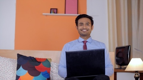 A young smiling businessman looking at laptop screen excited to get good news