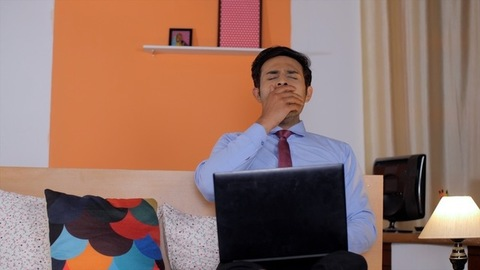 Smart young tired businessman sleeping while working on his laptop at home