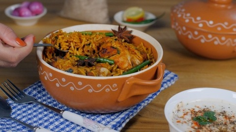 Female's hand tasting freshly made chicken Biryani with a spoon - tasty recipe