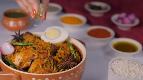 Woman's hand squeezing a slice of lemon juice before savoring it - Chicken Biryani, Indian recipe