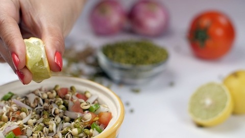 Female hands squeezing fresh lime juice into sprouts mixed with onions