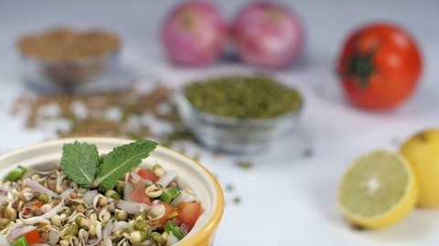 Fresh green mint leaves dropping on a bowl of sprouts salad - nutritious food