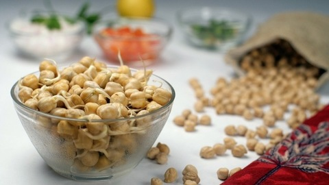 Dried raw chickpeas falling from a gunny bag on a white table - healthy food