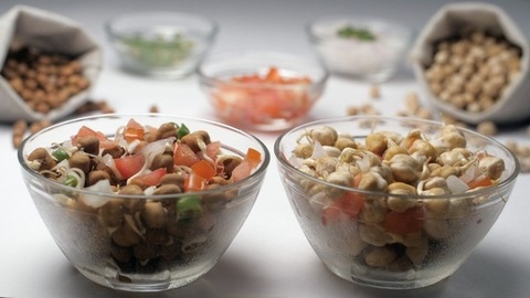 Two bowls of chickpeas salad mixed with onions and tomatoes - nutritious food