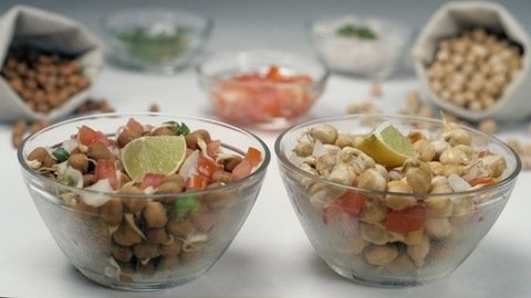 Two lemon slices falling inside a bowl of  sprouted chickpeas salad mixed with onions