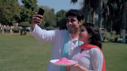 A woman standing with a plate of Gulal on Holi - Man clicking a selfie with her