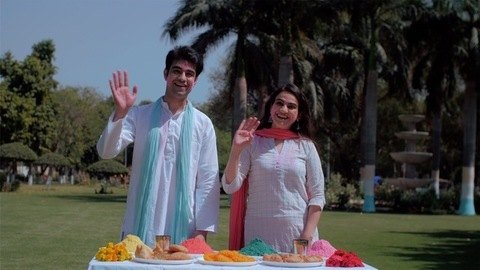 Happy Indian male and female wishing people for Holi festival standing outdoors