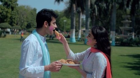 Beautiful woman feeding traditional Gujiya to an attractive male on Holi festival