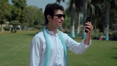 Smiling male adult chatting online during Holi party outdoors - festive mood