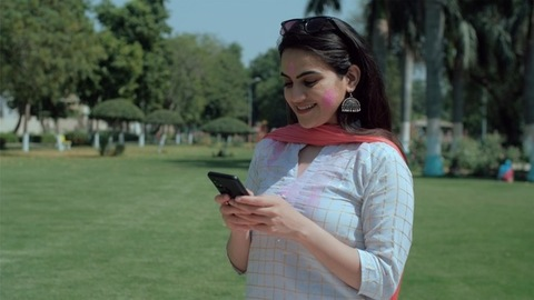 Gorgeous young female spending time on social media during Holi celebration