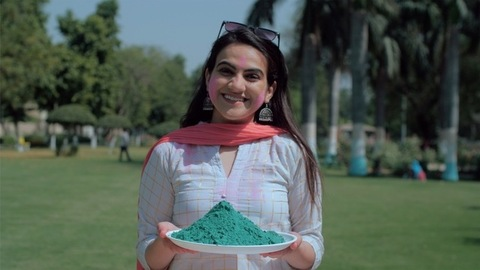 A lady wearing white Kurti standing with a Gulal plate on Holi