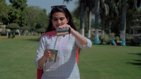 Cheerful young Indian woman mixing Thandai with two glasses during Holi party outdoors
